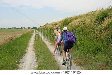 Family with Three people with two bicycles along the cycle path in the nature reserve