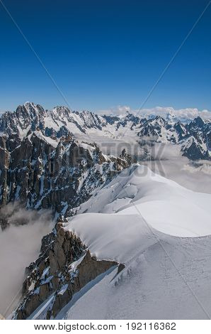 View of snowy peaks from the Aiguille du Midi, in French Alps Chamonix Mont Blanc, alpine mountains landscape, clear blue sky in warm sunny summer day.