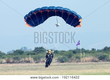 Female Skydiver Making Safe Landing On Grass With Open Brightly Colourful Parachute.