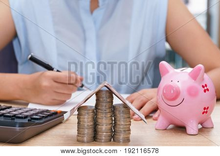 Woman hand writing with pink piggy bank on wooden desk - save money to buy house concept