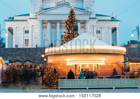 Helsinki, Finland - December 11, 2016: Xmas Market On Senate Square With Holiday Carousel And Famous Landmark Is Lutheran Cathedral And Monument To Russian Emperor Alexander II At Winter Evening.