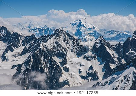Close up of snowy peaks, view from the Aiguille du Midi, in French Alps Chamonix Mont Blanc, alpine mountains landscape, clear blue sky in warm sunny summer day