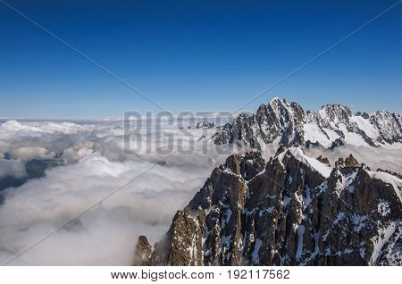 View of snowy peaks from the Aiguille du Midi, in French Alps Chamonix Mont Blanc, alpine mountains landscape, clear blue sky in warm sunny summer day