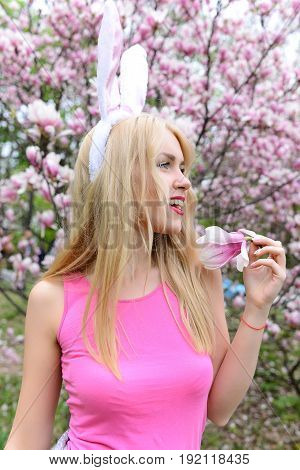 girl in bunny ears with magnolia branch near blossoming tree