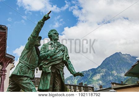 Chamonix, France - June 26, 2016. Statue in honor of Balmat and Paccard with alpine landscape in Chamonix, a famous ski resort in Haute-Savoie Province, at the foot of Mont Blanc in the French Alps