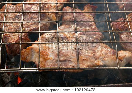 Close Up View Of Juicy Pork Steak Cooking On An Open Flame Grill..