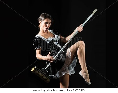 pretty sexy girl or maid in housemaid uniform apron dancing with mop as guitar on black background housekeeping and cleaning