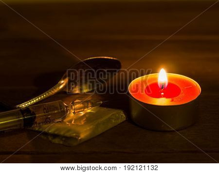 Cocaine inserts are placed on injection a wooden table with cocaine bags spoon and candles.