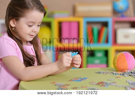 Portrait of a cute little girl collecting puzzles