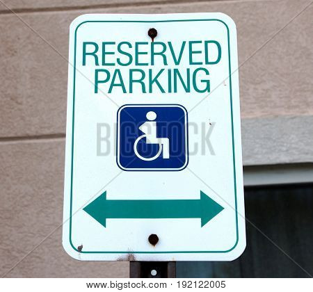 A sign with a picture of a person in a wheelchair that reads reserved parking is posted at in a parking lot