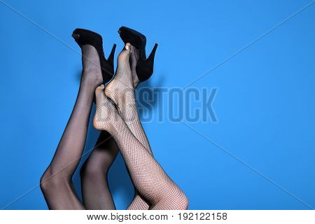 sexy legs of girls in fashionable tights and shoes mixed on blue background couple in love lesbian copy space