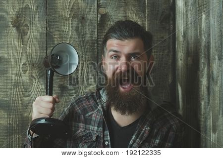 hipster or bearded caucasian man with long beard and moustache shouting with electric lamp with light bulb on grey wooden wall. Electricity and lightning. Idea and innovation