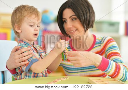 Young mother playing with cute little son