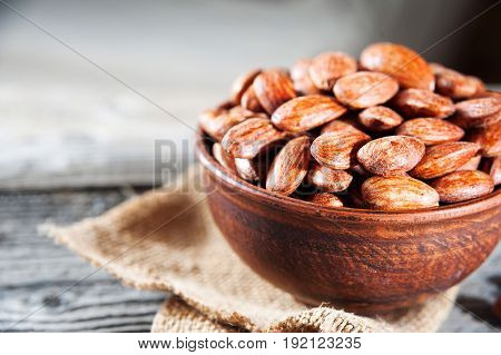 Roasted Almonds In Bowl On Wooden Table