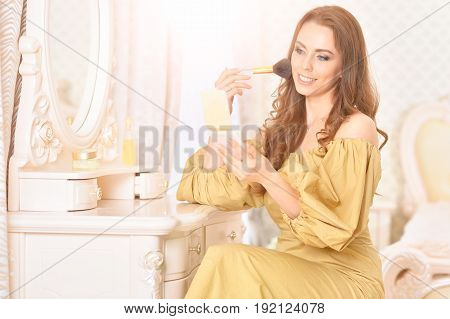 Attractive young woman in golden dress applying makeup in front of mirror