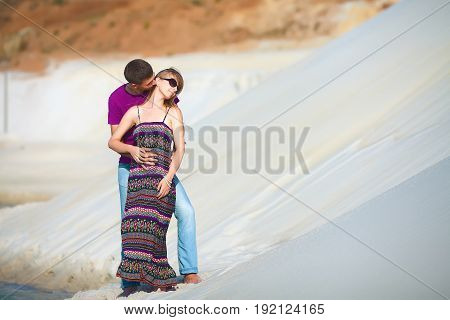 lovers on romantic travel honeymoon vacation summer holidays romance. Young happy couple kissing on the beach, caucasian woman and man embracing and kissing outdoors