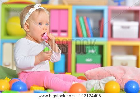 Adorable little child playing with colorful toys in childrens room