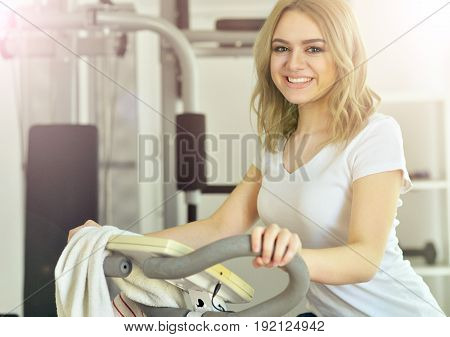 Sporty young woman training in gym cycling