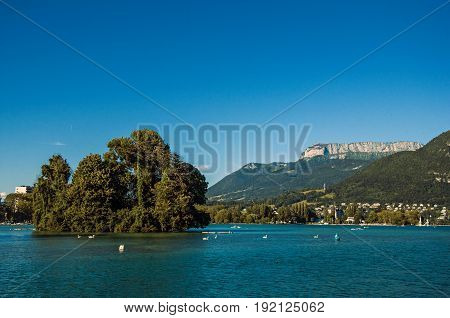 View of Annecy lake, with island, vegetation, mountains and blue sky in background. Located in the department of Haute-Savoie, Auvergne-Rhône-Alpes region, in south-eastern France