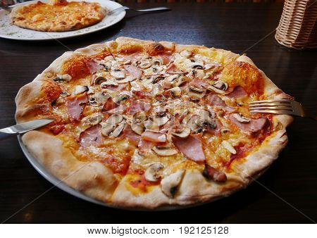 A pizza with mushrooms cheeze and ham