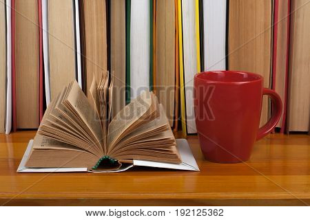 Open book, red cup hardback colorful books on wooden table. Back to school. Copy space for text. Education business concept