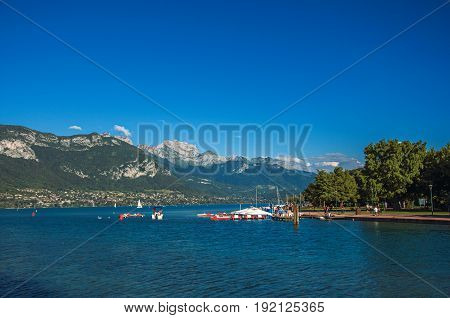 View of Annecy lake, with island, vegetation, boats, mountains and blue sky in background. Located in the department of Haute-Savoie, Auvergne-Rhône-Alpes region, in south-eastern France