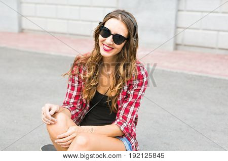 Young smiling woman relaxing and listening to music with headphones in the street