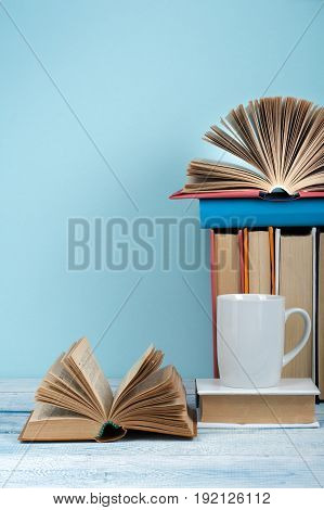 Open book, hardback books on wooden table and blue background. Back to school. Copy space for text