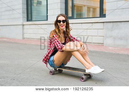 Young woman sitting on the skater. Smiling woman with skateboard in outdoors.