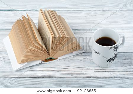 Open book, coffee cup and snack on wooden table background