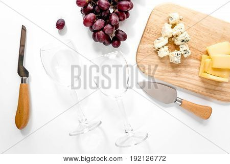 Composition with wineglasses, cheese and grape on white background.