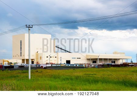 A small factory in the background of a cloudy sky. View from outside
