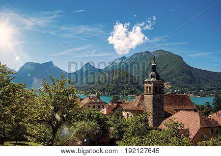 View of houses with belfry, in the village of Talloires, next to the Lake of Annecy. Mountains landscape on background, blue sky with clouds. France. Retouched photo