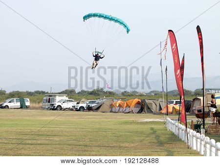 Male Skydiver Coming In For Landing On Grass With Open Brightly Coloured Parachute.