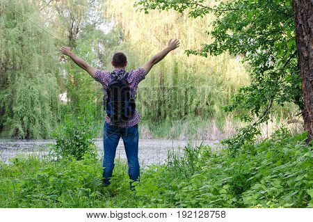 Guy With A Backpack Is Standing On The Shore Of A Forest Lake With Arms Outstretched, A Back View