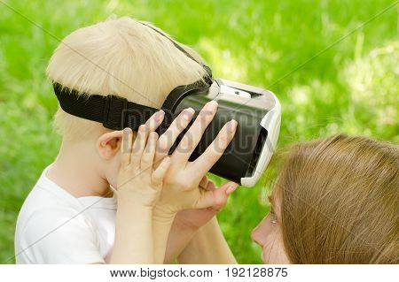Mom corrects his son glasses of virtual reality against the background of green grass