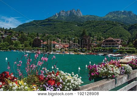 Pier with flowers on the lake of Annecy, in the village of Talloires. Mountains landscape, village and blue sky on background. France