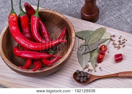 Red chili pepper on plate on grey background.