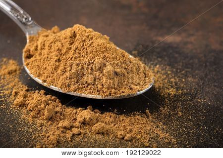 Spoon filled with cinnamon powder on rusty background