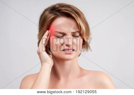 Woman having headache migraine, head pain .