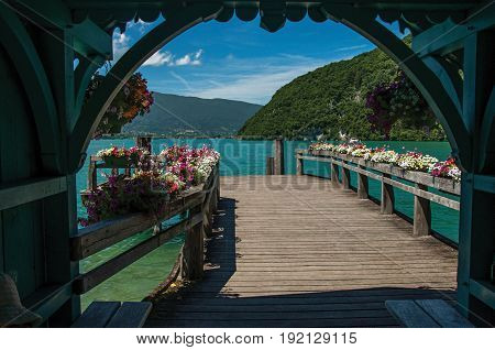 Pier with flowers on the lake of Annecy, in the village of Talloires. Mountains landscape and blue sky on background. France