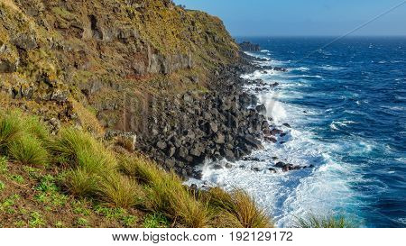 Wide angle view of volcanic coast with high cliffs in Terceira, Portugal