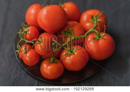 Bunch of Fresh red ripe tomatoes with branches with water drops, wooden plate, black background. Selective focus. Top view. Concept of vegetarian and healthy food