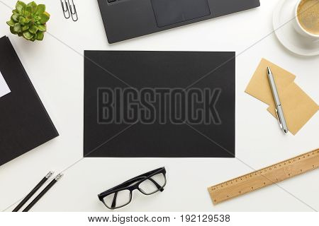 White office desk with black paper in center, coffee and supplies. Top view with copy space.