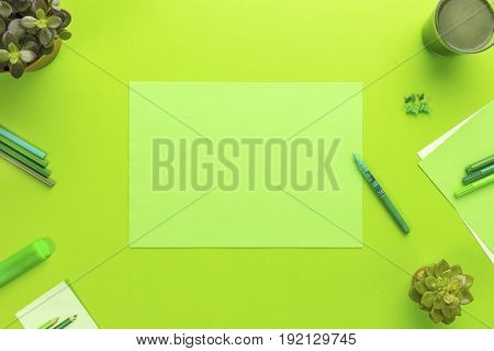 High angle view of a environmental concept of a green office desk with supplies, green algae drink and plants. Living green and save the planet. Top view with copy space.