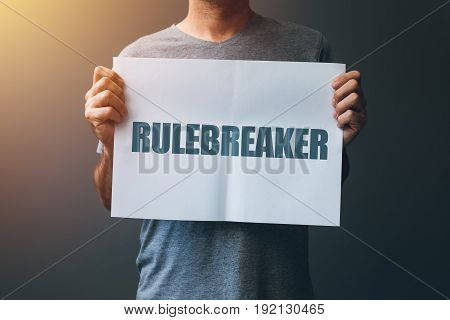Rulebreaker attitude person who breakes the rules concept with male holding poster
