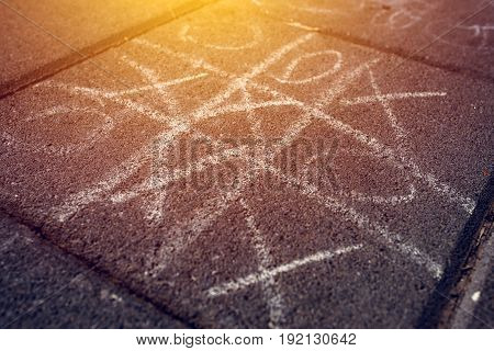 Strategic game of tic tac toe played on street pavement selective focus