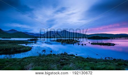 Reflections of the late evening sky on midsummer in the small lochan on Rannoch Moor near Glencoe in Scottish Highlands