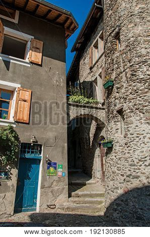 Conflans, France - June 29, 2016. Alley with arch and buildings, in the city center of the medieval hamlet of Conflans, department of Haute-Savoie, Auvergne-Rhône-Alpes region, south-eastern France