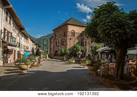 Conflans, France - June 29, 2016. Square with stone building and shops in the city center of Conflans, a medieval hamlet in Haute-Savoie department, Auvergne-Rhône-Alpes region, south-eastern France